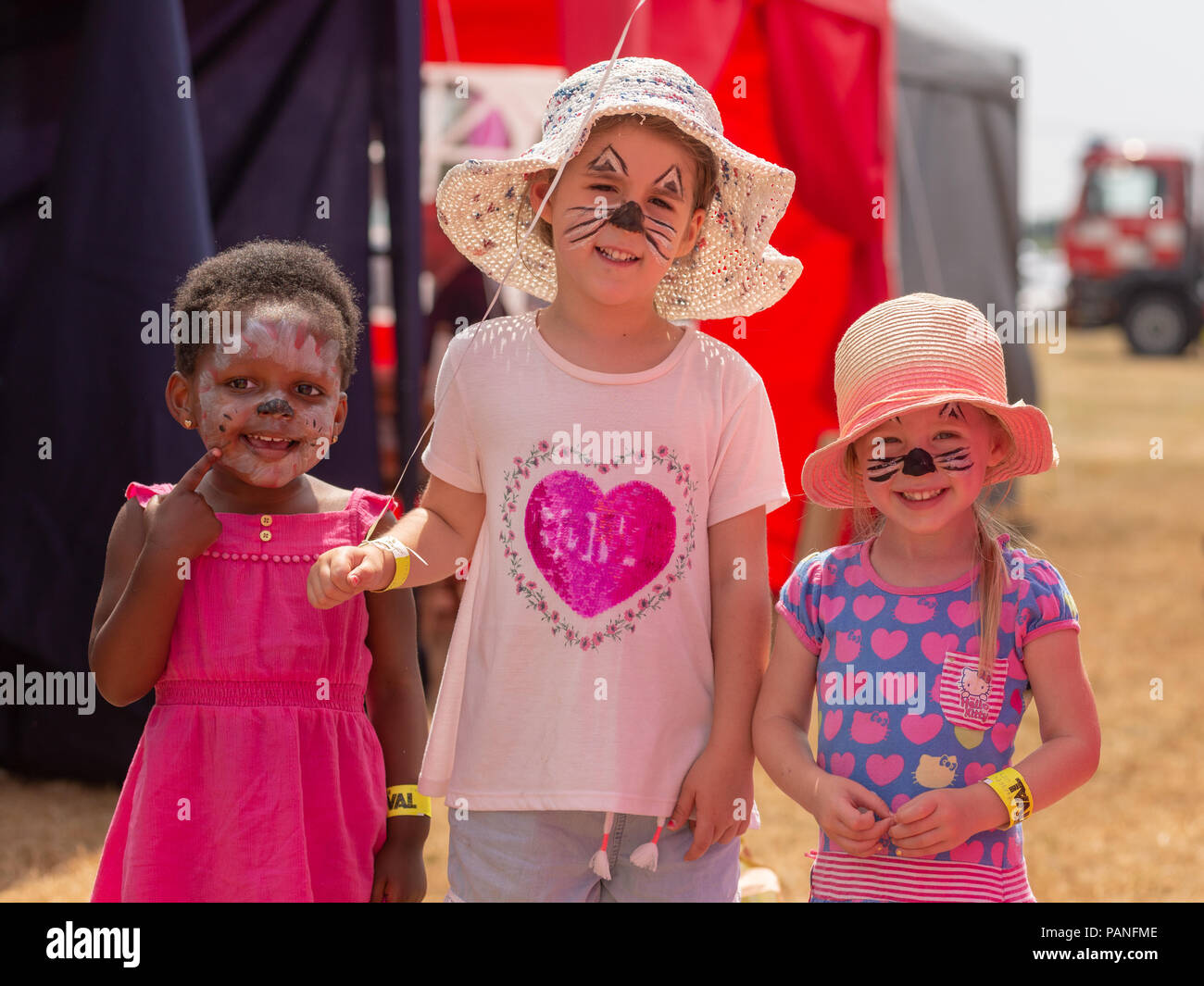 Three young girls with painted faces and smiling at a country fair in Hampshire in summer - Stock Image