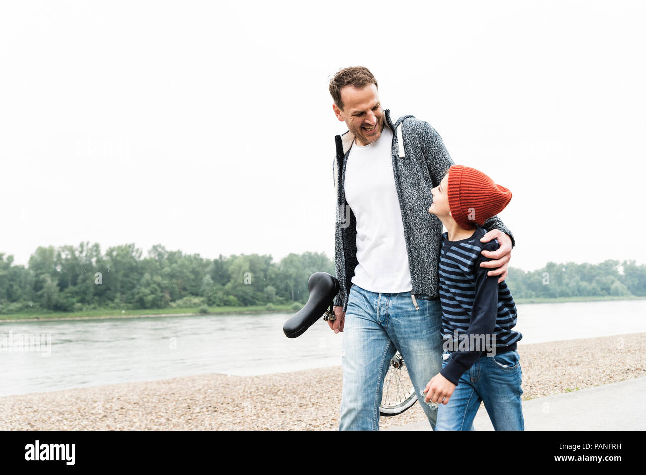 Happy father and son walking with unicycle at the riverside - Stock Image