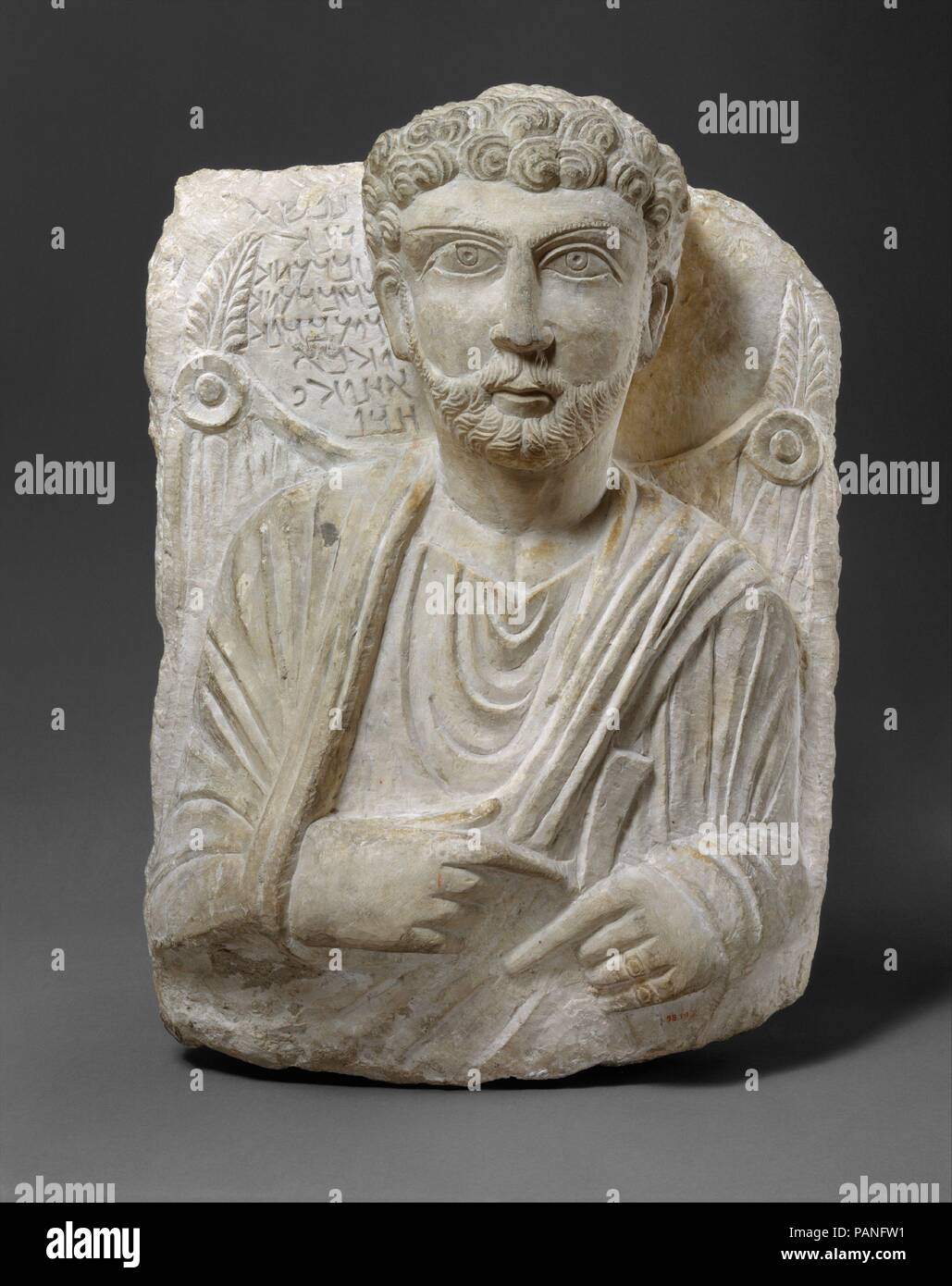 Funerary relief. Dimensions: 20 5/8 × 15 1/8 × 7 5/8 in., 98 lb. (52.4 × 38.4 cm). Date: ca. 150-200.  Inscription:  1-2 This image   3 (is of) Zabda'ateh,   4 son of Zabda'ateh,   5 which made for him   6 Wahba,   7 his brother.   8 Alas!  Transliteration:  1 nps?  2 dnh  3 zbd?th  4 br zbd?th  5 dy ?bd lh  6 whb?  7 ?hwhy  8 hbl  This relief is a type of funerary monument characteristic of the prosperous caravan city of Palmyra during the first three centuries A.D. Reliefs with a representation of the deceased and a short identifying inscription were used to seal burial niches in elaborately - Stock Image