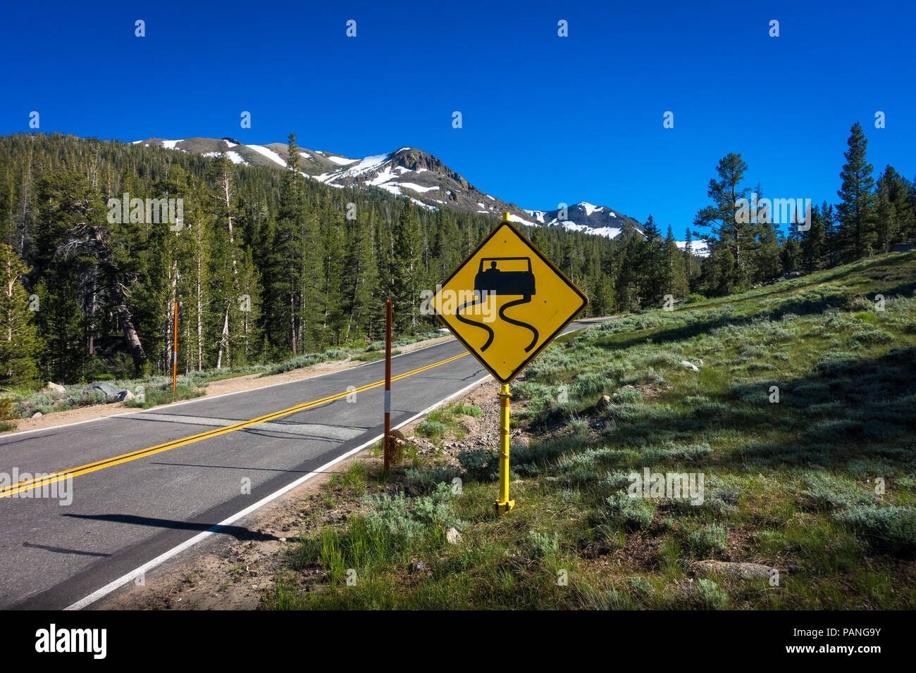 Yellow 'slippery road' sign with snowy forest peaks - Highway 108 Roadside, California - Stock Image