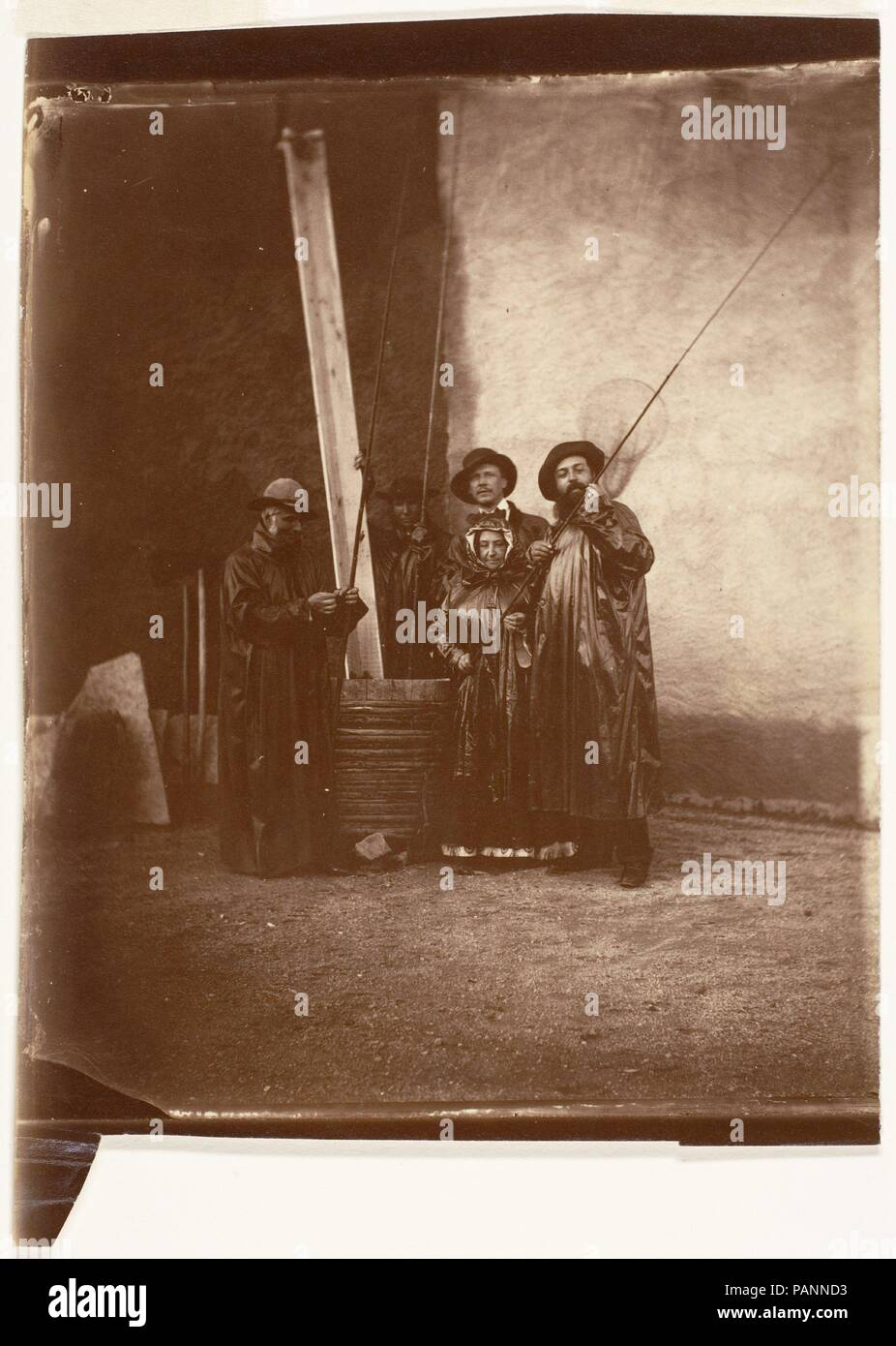 [The Artist, His Mother, and Friends in Fishing Garb]. Artist: Olympe Aguado de las Marismas (French, Paris 1827-1894 Compiegne). Dimensions: Image: 17.7 × 14.6 cm (6 15/16 × 5 3/4 in.)  Sheet: 19 × 14.6 cm (7 1/2 × 5 3/4 in.), irregularly trimmed. Date: ca. 1860.  The photographer Count Olympe Aguado de las Marismas was a wealthy aristocrat and a familiar figure at the court of Napoleon III. At an informal gathering at one of his country houses, Aguado posed his family and friends as fishermen, complete with long poles, a fine net, and foul-weather gear made of oilcloth. Although her elegant  - Stock Image