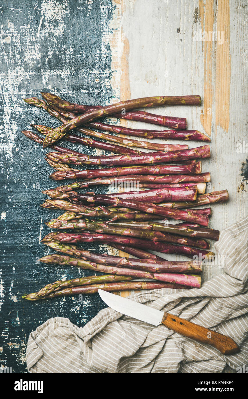 Fresh purple asparagus over rustic wooden background, vertical composition - Stock Image