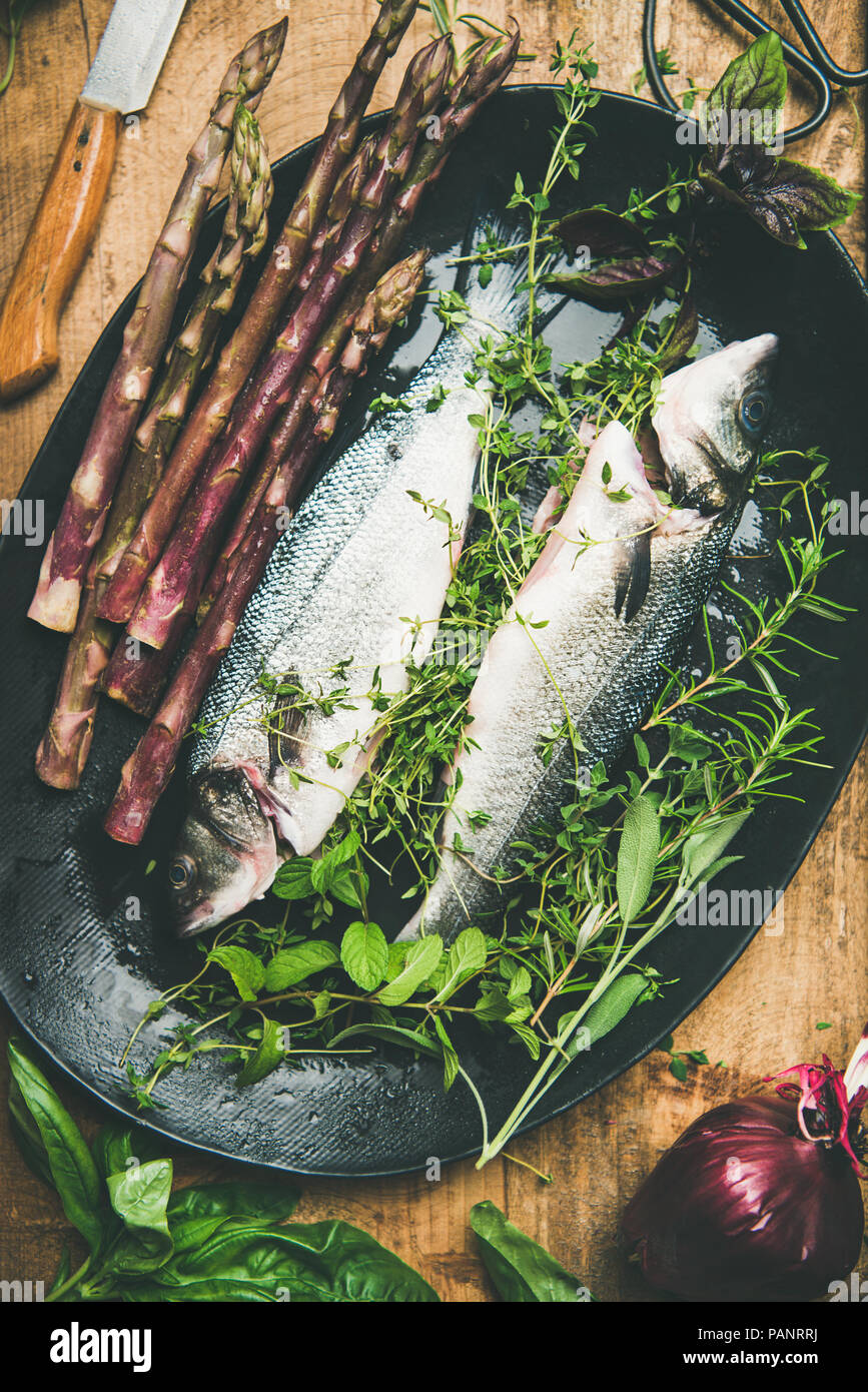 Raw uncooked sea bass fish with herbs and vegetables - Stock Image