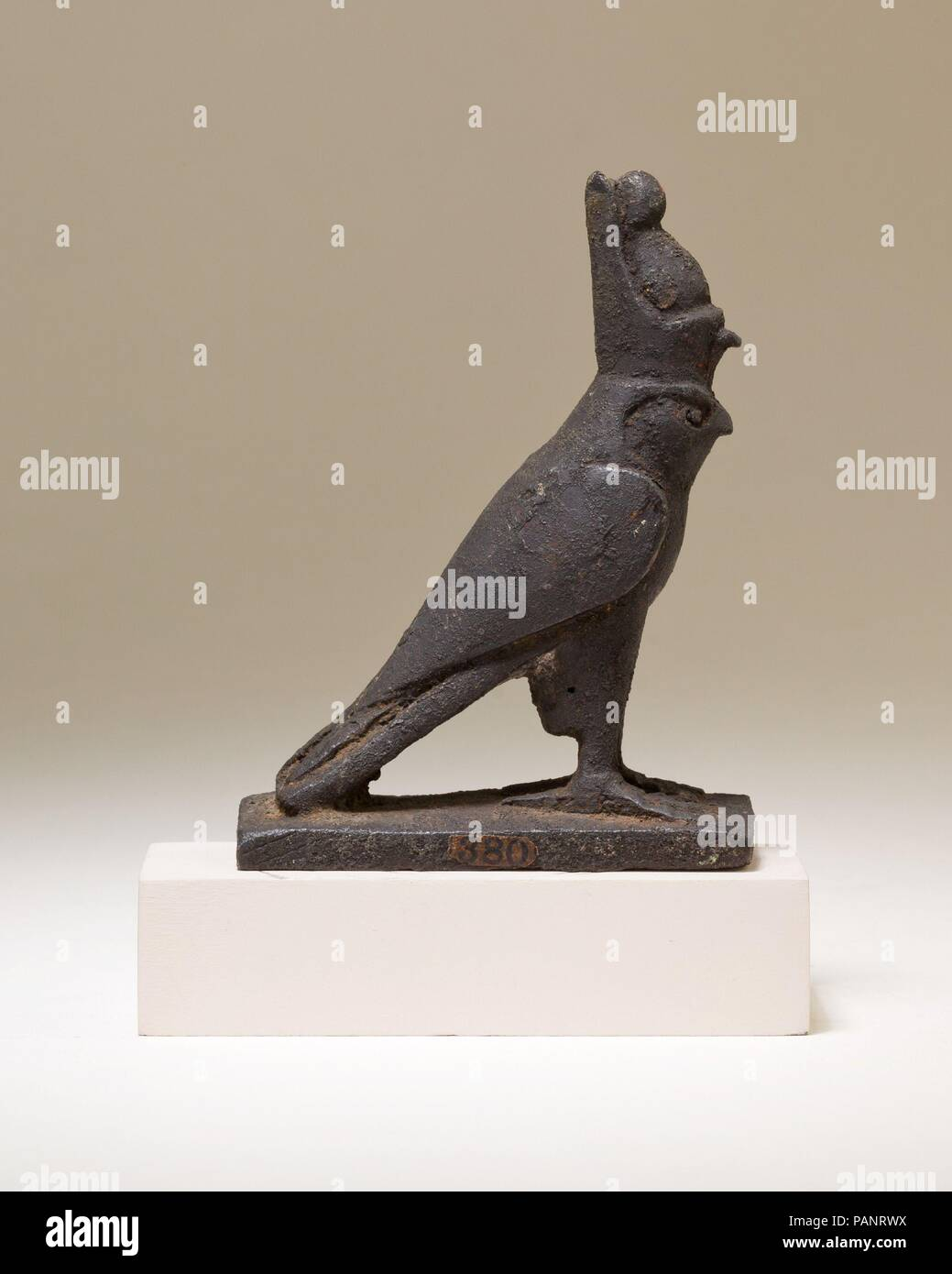 Horus falcon figure. Dimensions: H. 8.2 cm (3 1/4 in.); W. 2.5 cm (1 in.); L. 6.3 cm (2 1/2 in.). Date: 664-30 B.C..  The falcon god Horus stands with his wings swept back. He wears the double crown of Egypt, a royal crown that symbolizes the union of Lower and Upper Egypt, and highlights Horus' role as the legitimate ruler of the entire land. The falcon wears the double crown because Horus and the concept of kingship were closely tied, as early as the Predynastic Period.   The falcon stands on a rectangular platform, which could have functioned in a number of ways. The figure could have been  - Stock Image