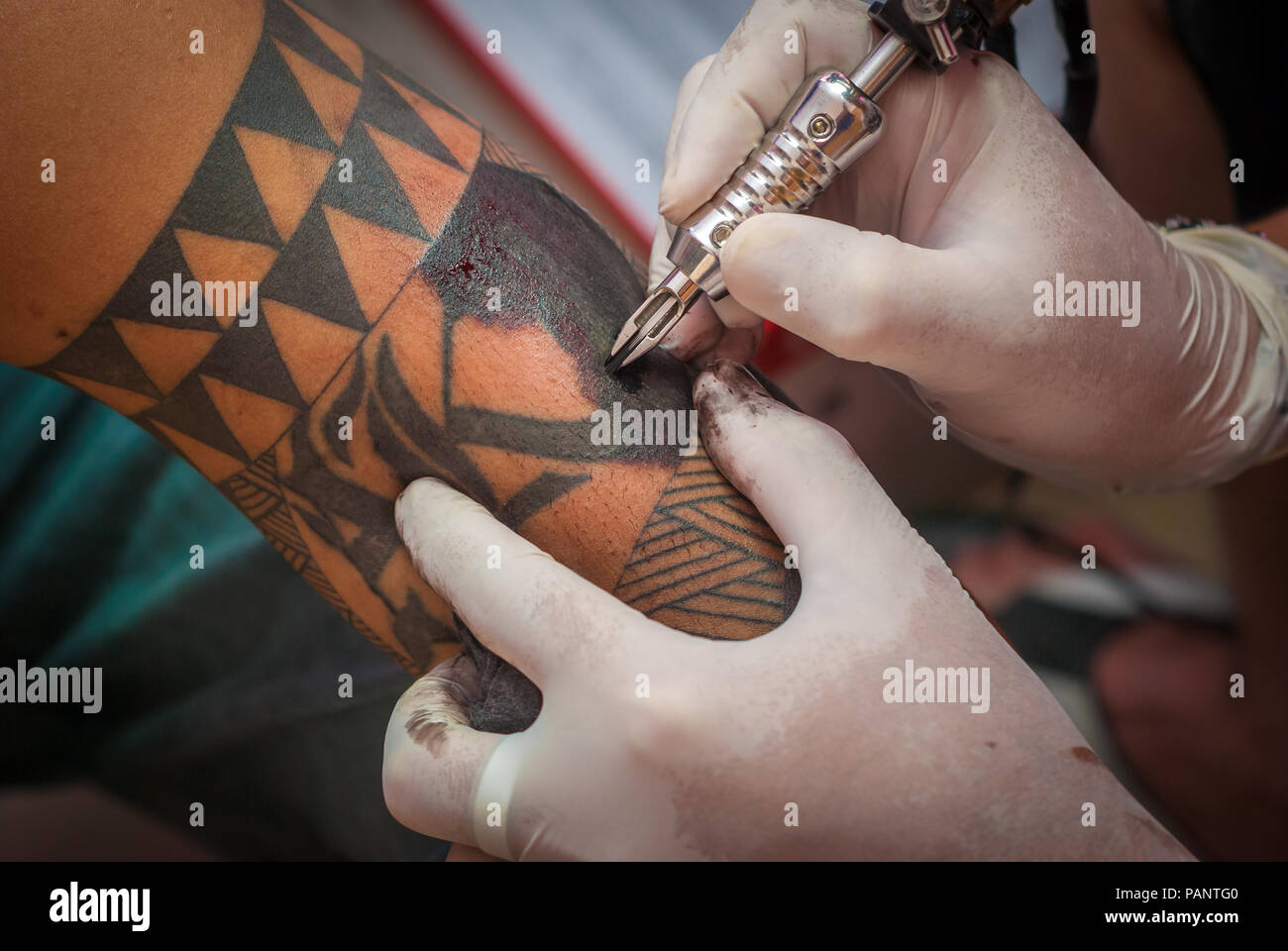 Unknown man having his tattoo made by a tattoo artist - Stock Image
