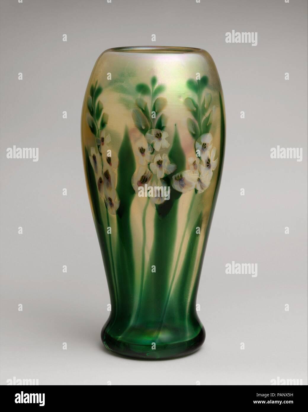 Vase. Culture: American. Designer: Designed by Louis Comfort Tiffany (American, New York 1848-1933 New York). Dimensions: 16 7/16in. h. (41.8cm)  Body diameter: 8 in. (20.3 cm)  Foot diameter: 5 7/8 in. (14.9 cm). Maker: Tiffany Furnaces. Date: ca. 1909. Museum: Metropolitan Museum of Art, New York, USA. - Stock Image
