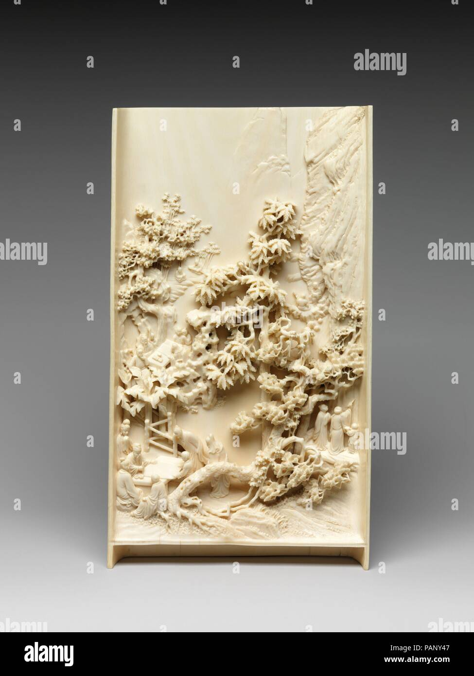 Table screen with figures in a landscape. Culture: China. Dimensions: H. 11 1/8 in. (28.3 cm); W. 6 3/8 in. (16.2 cm); D. 1 1/16 in. (2.7 cm). Date: 18th century.  Three sets of figures are nestled in the towering mountains on this screen, which would have been displayed in a scholar's studio. The two groups at left are shown huddled around a table on which an individual writes or paints. At right, a figure appears to be writing or carving on the wall of a cliff, a common practice in such literati gatherings. Museum: Metropolitan Museum of Art, New York, USA. - Stock Image