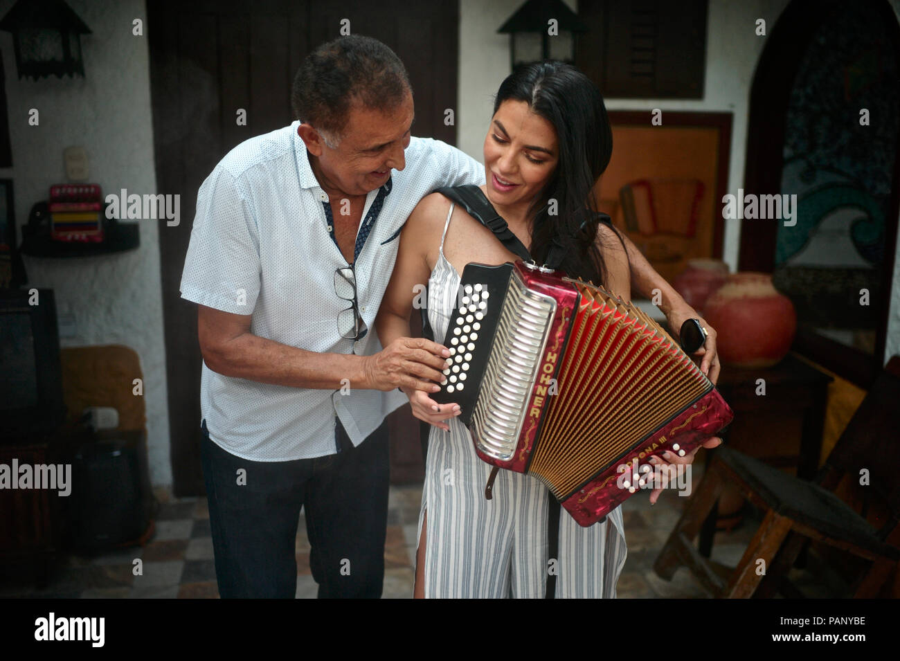 Colombian vallenato composer Beto Murgas teaches CBS Colombian-American reporter Astrid Martinez to play the accordion at his home, the accordion muse Stock Photo