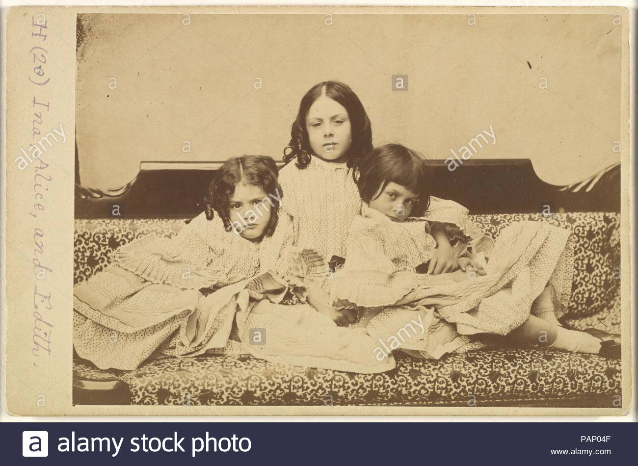 Edith, Ina and Alice Liddell on a Sofa. Artist: Lewis Carroll (British, Daresbury, Cheshire 1832-1898 Guildford). Dimensions: Mount: 4 3/16 in. × 6 7/16 in. (10.7 × 16.3 cm)  Image: 4 1/16 × 6 1/16 in. (10.3 × 15.4 cm). Person in Photograph: Person in photograph Alice Pleasance Liddell (British, 1852-1934); Person in photograph Edith Mary Liddell (British, 1854-1876); Person in photograph Ina Liddell (British, 1849-1930). Date: Summer 1858. Museum: Metropolitan Museum of Art, New York, USA. - Stock Image