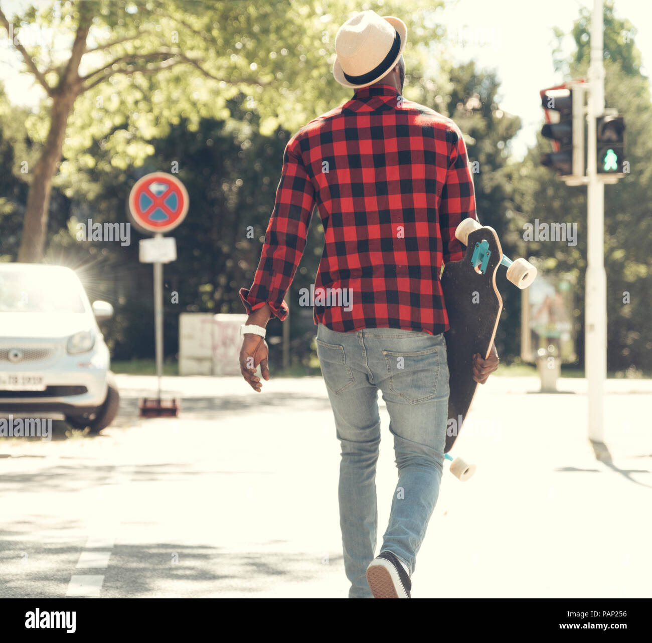 Cool young man with skateboard walking in the city, - Stock Image