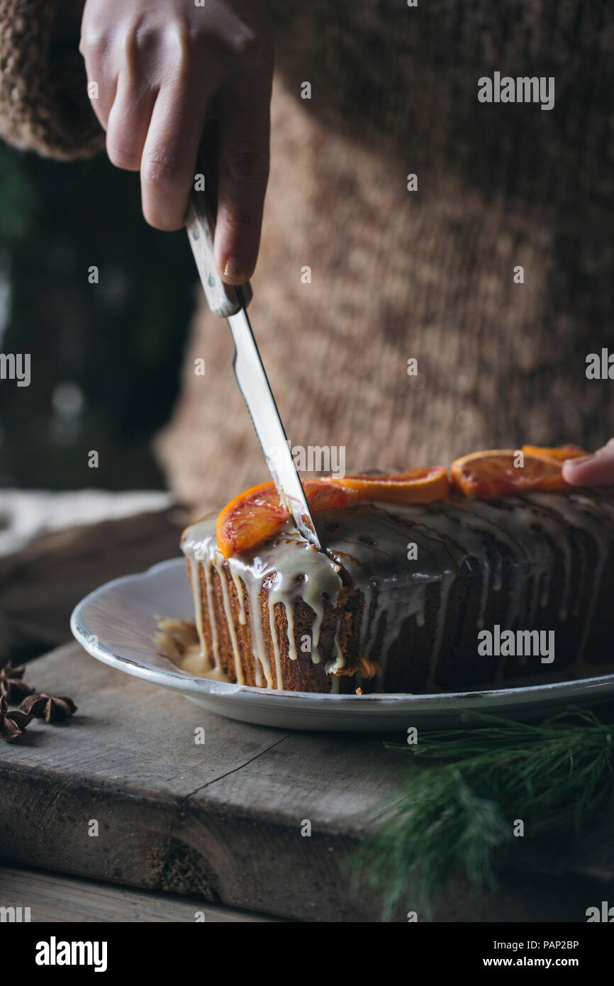 Woman's hand cutting home-baked Christmas cake, partial view - Stock Image