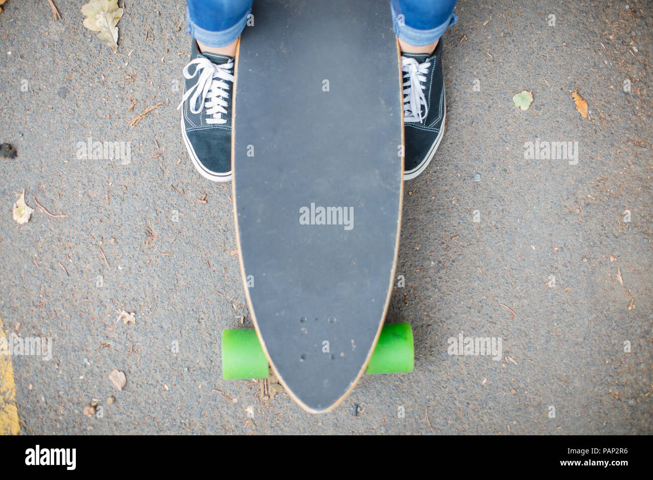 Close-up of feet next to skateboard - Stock Image