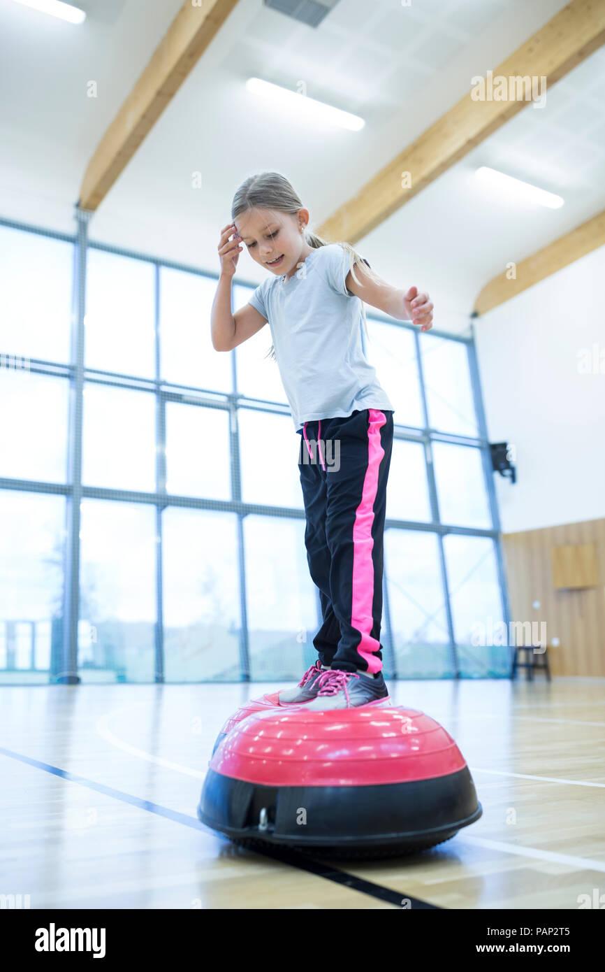 Schoolgirl balancing on exercise equipment in gym class - Stock Image