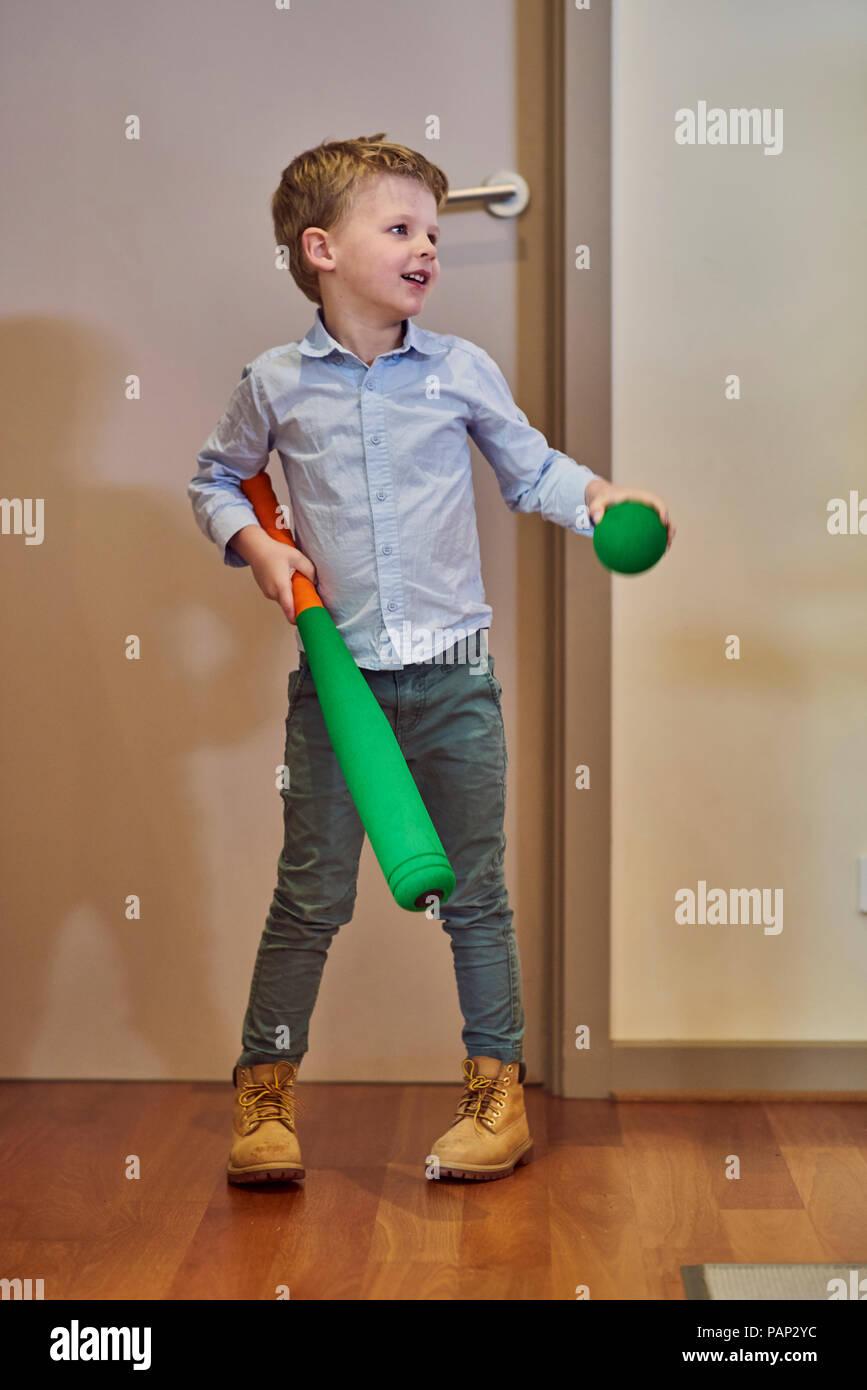 Boy at home holding foam baseball bat and ball - Stock Image