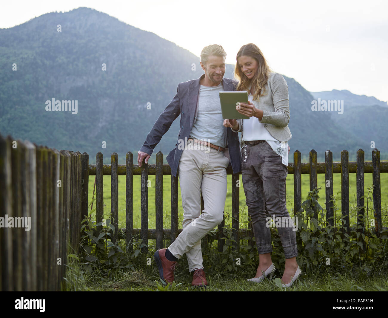 Man and woman sharing tablet in rural landscape - Stock Image