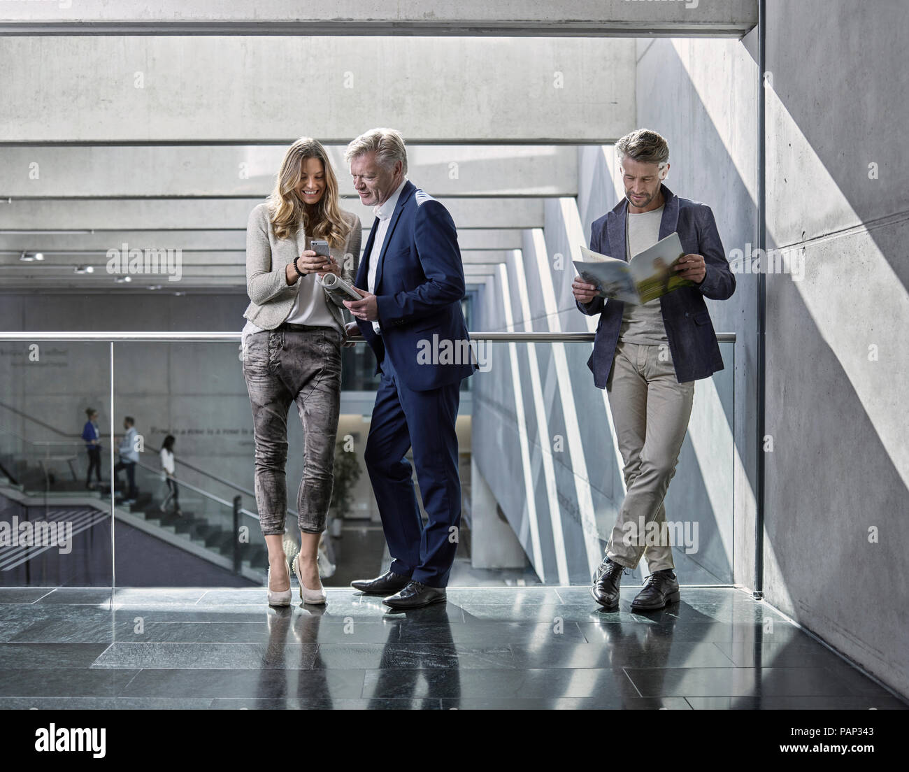 Business people talking on office floor - Stock Image