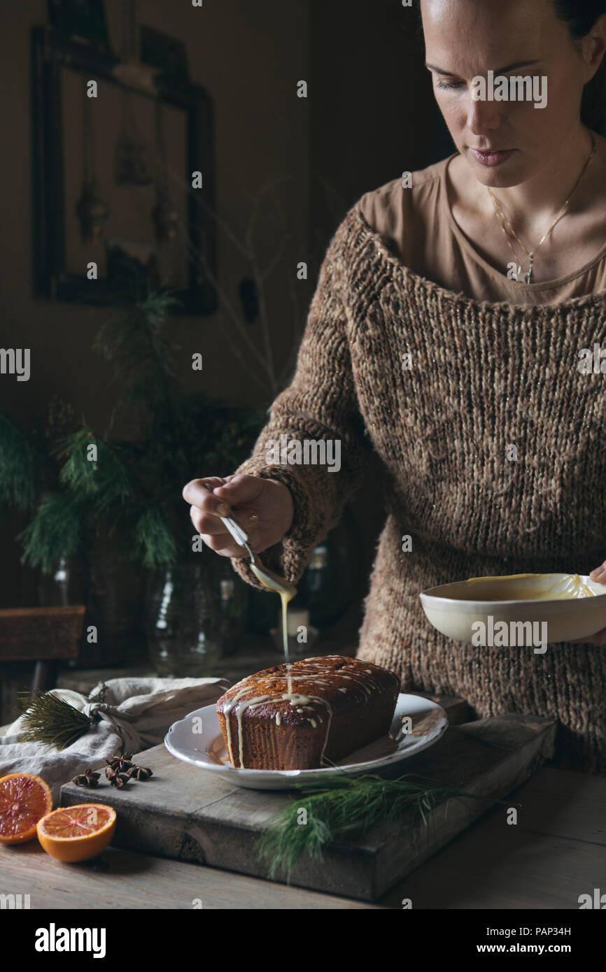 Woman preparing home-baked Christmas cake - Stock Image