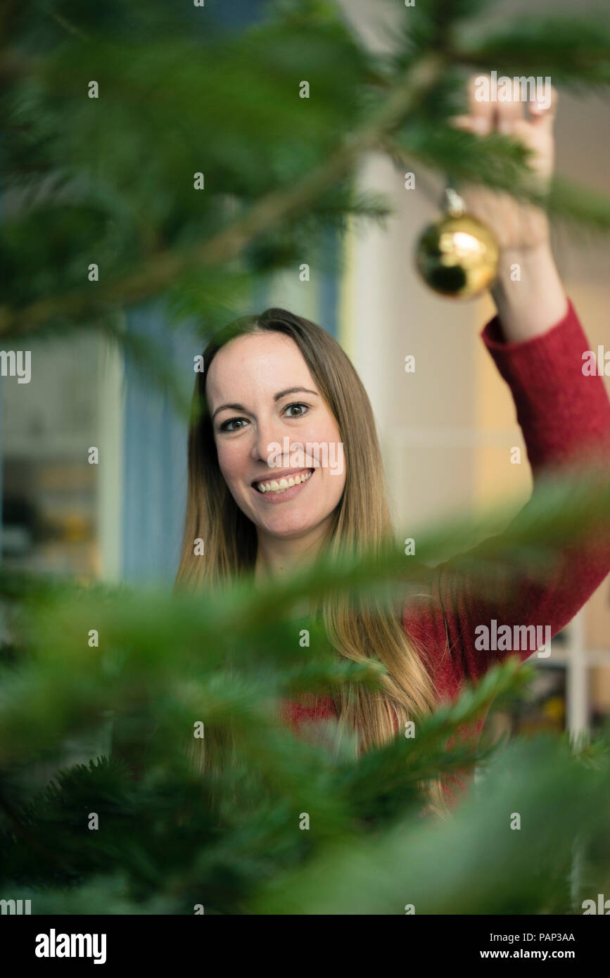 Portrait of smiling woman decorating Christmas tree - Stock Image