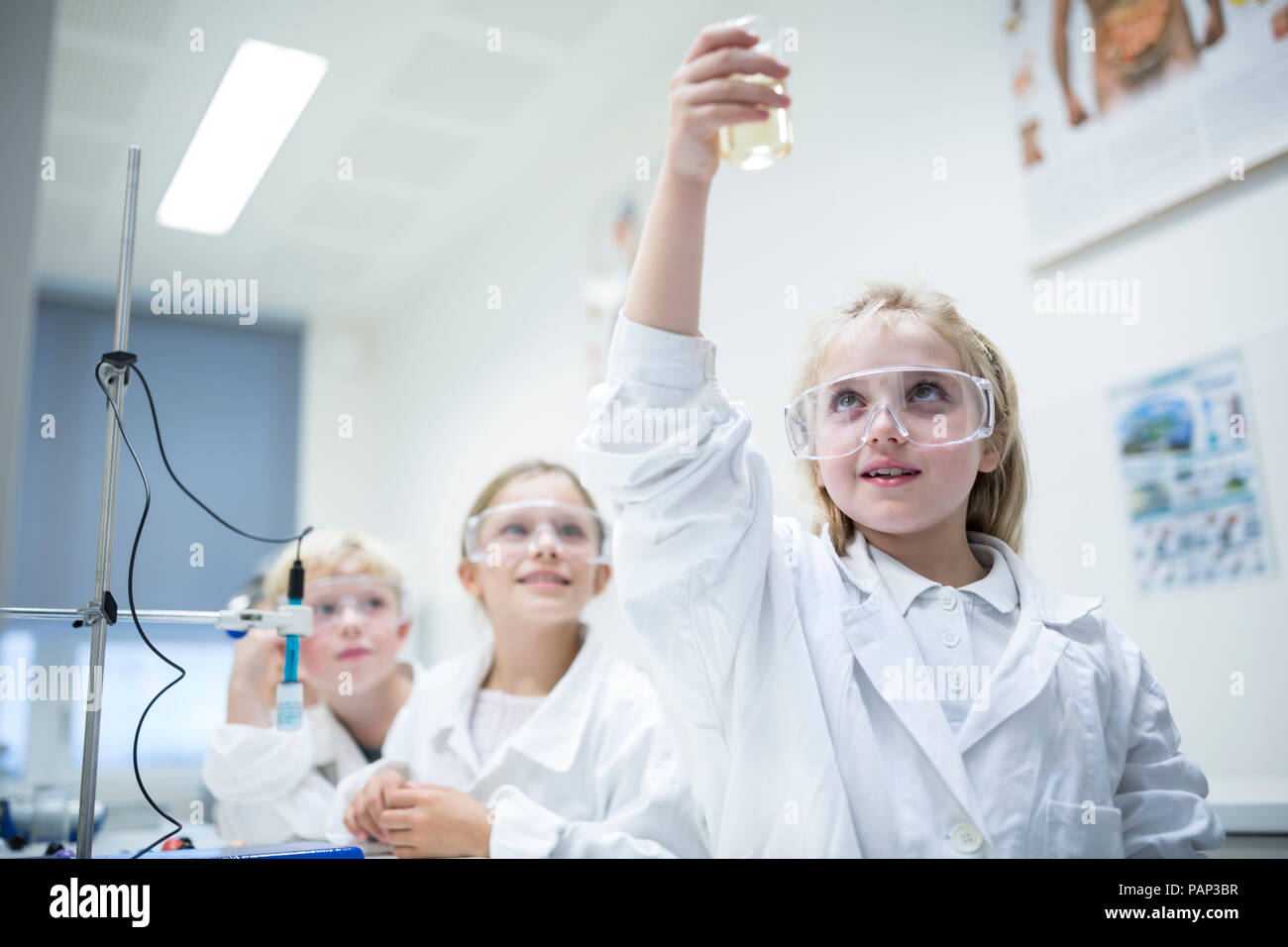 Pupils in science class experimenting with liquid - Stock Image
