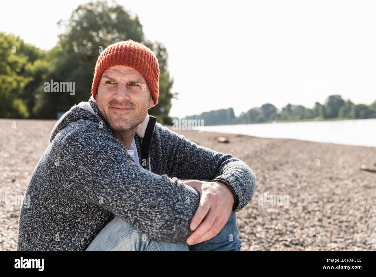 Mature man wearing red beanie sitting at Rhine riverbank Stock Photo