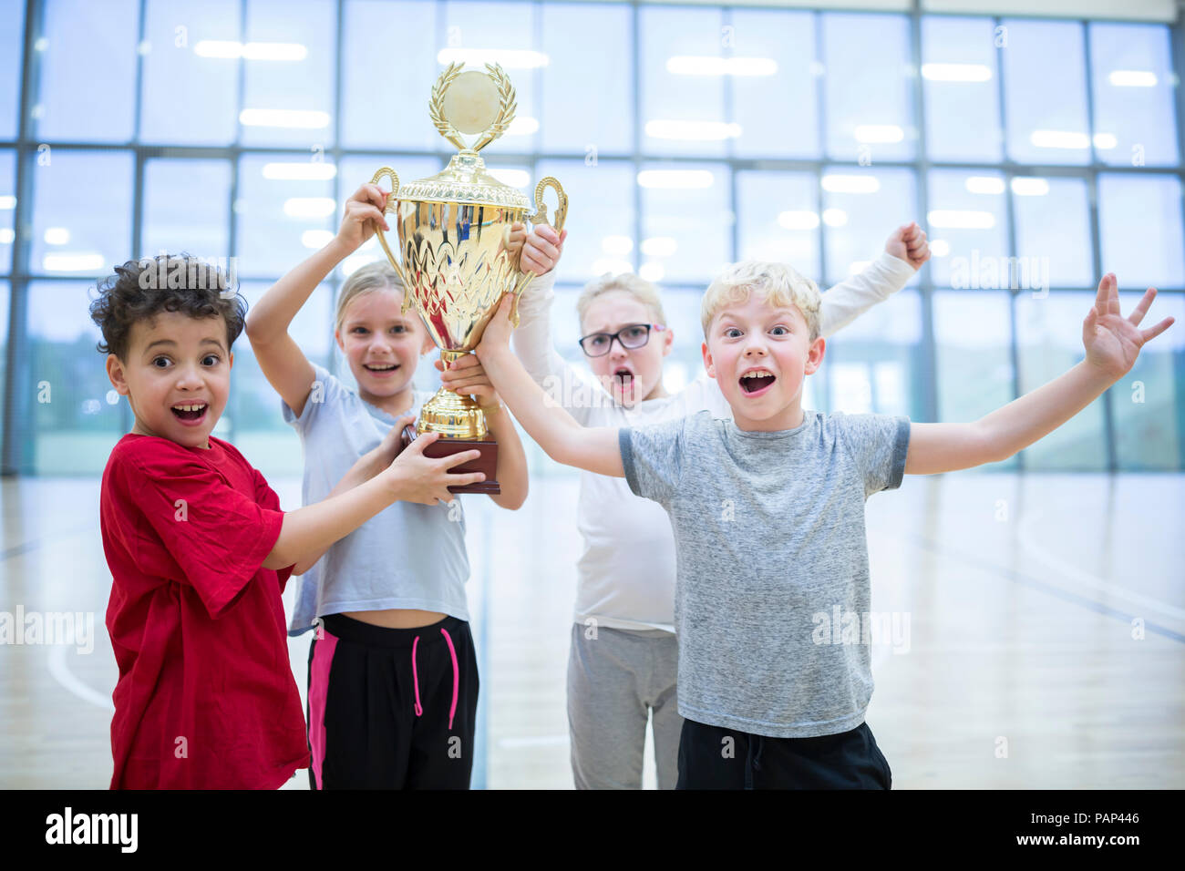 Happy pupils holding trophy in gym - Stock Image