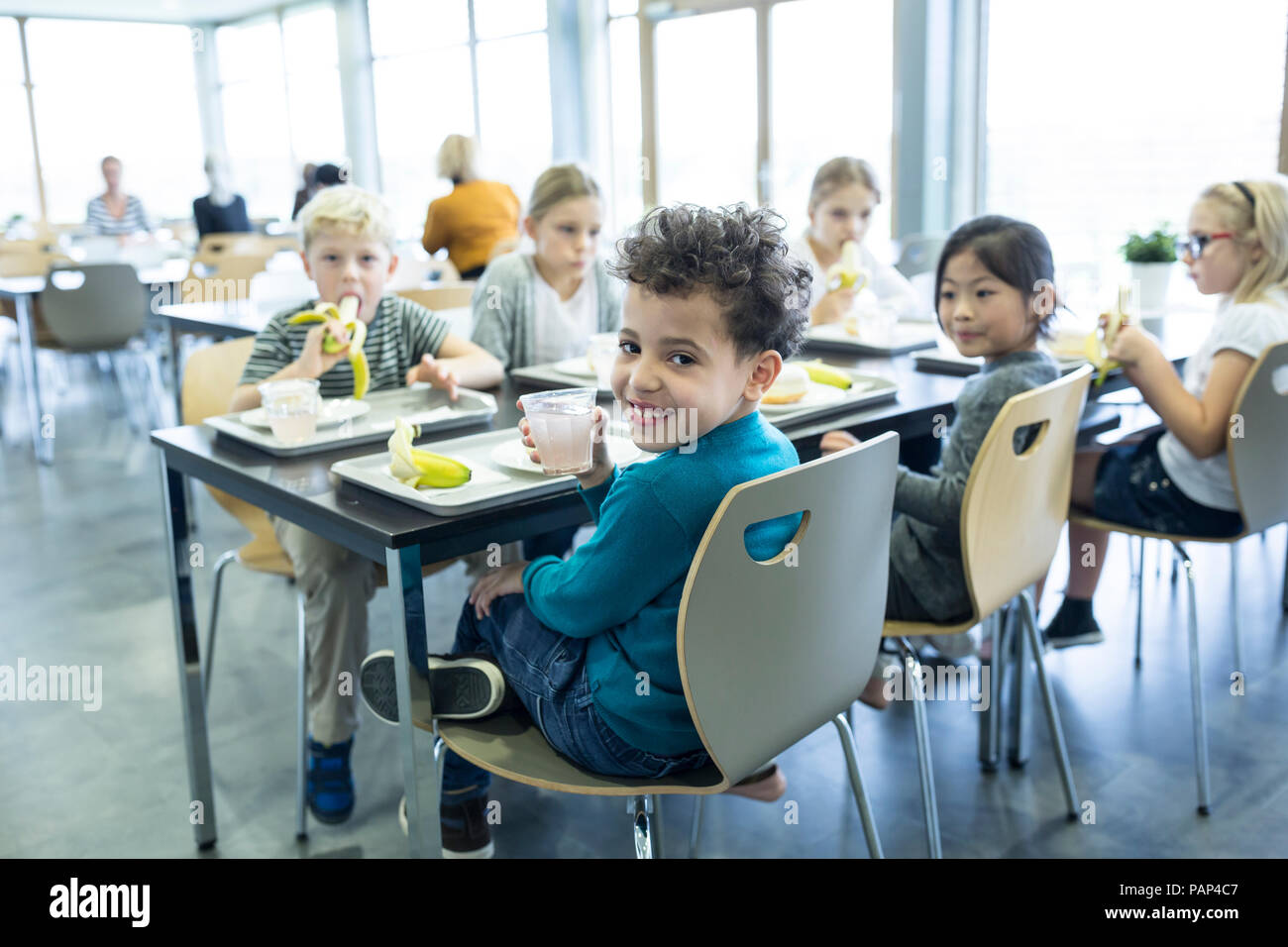 Pupils having lunch in school canteen - Stock Image