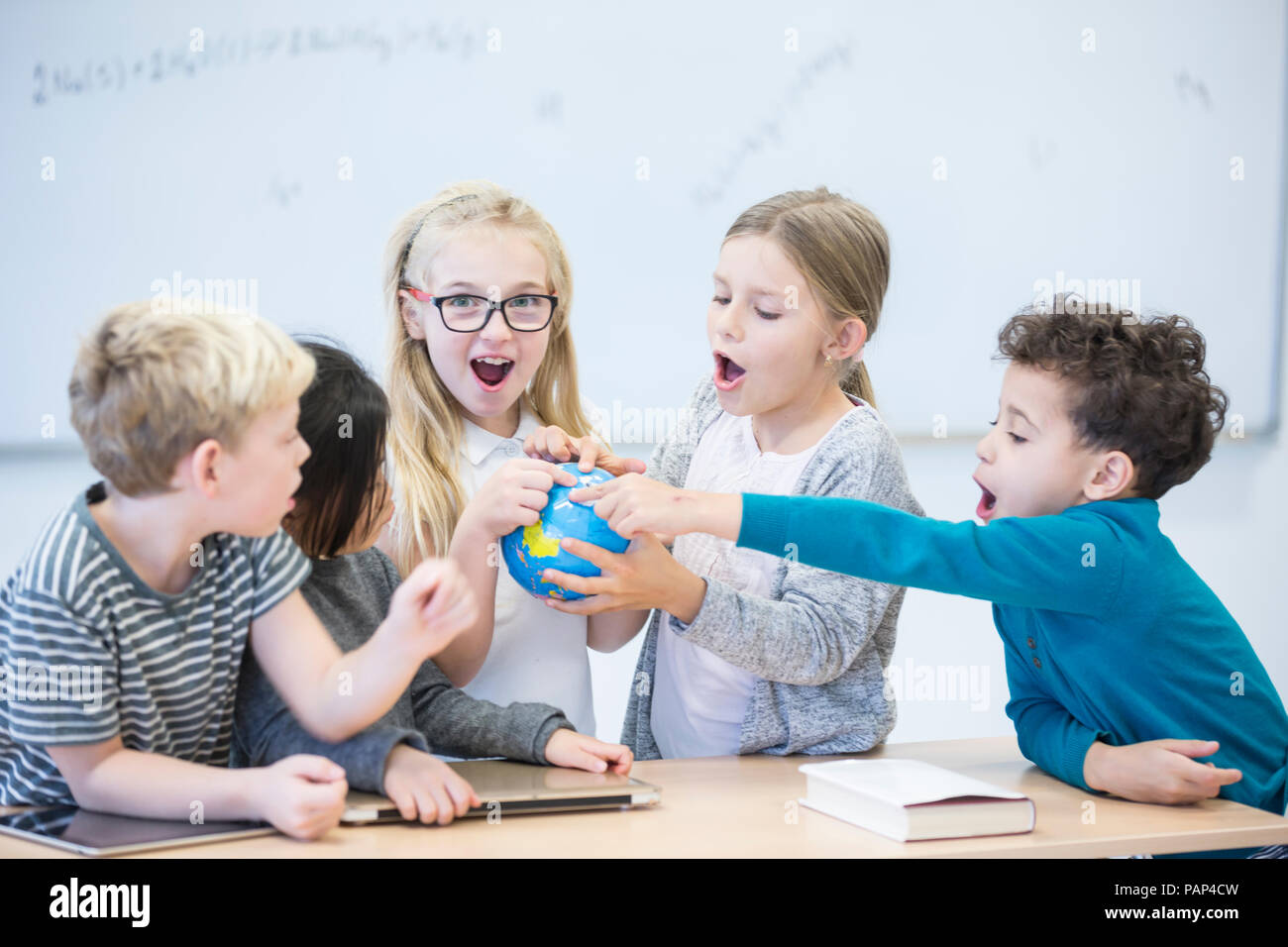 Happy pupils holding globe together in class - Stock Image