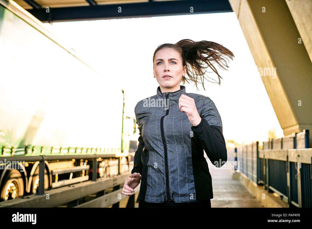 Portrait of sportive woman jogging - Stock Image
