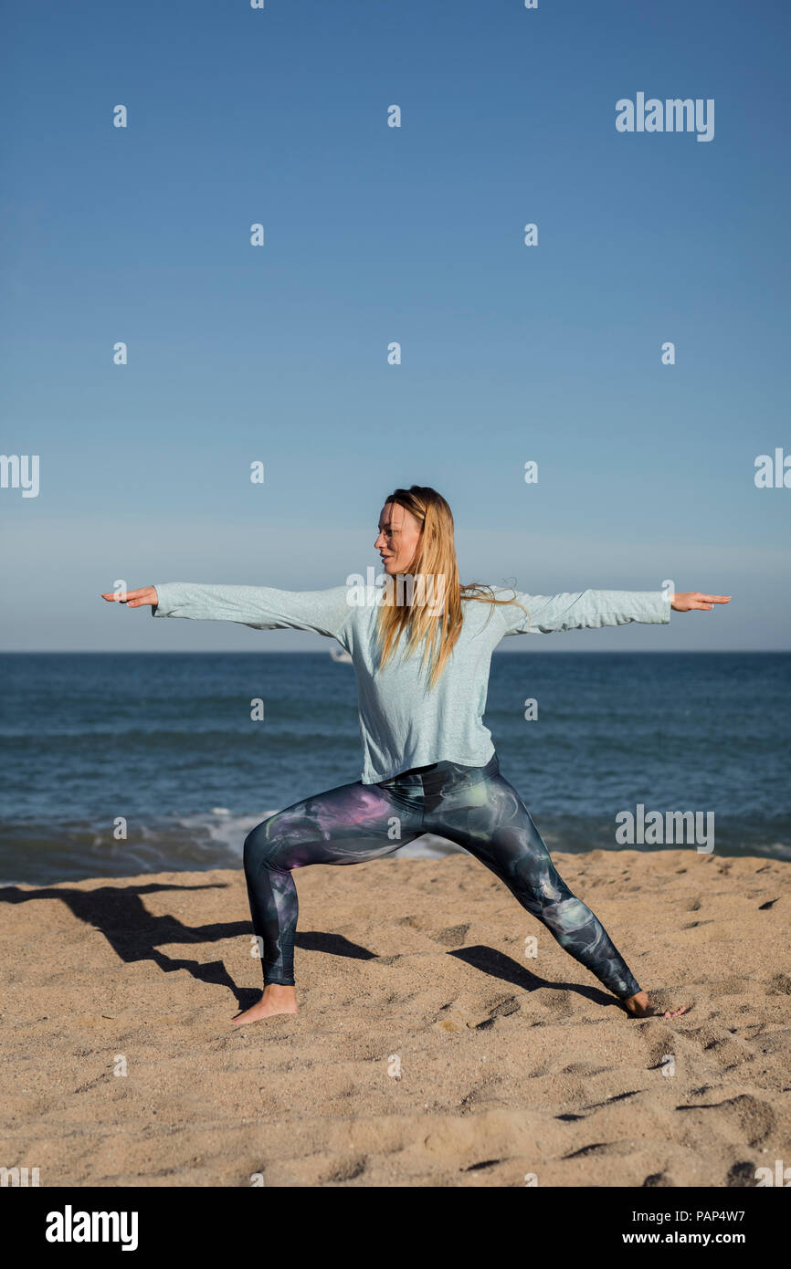 Woman doing yoga on the beach, warrior pose - Stock Image