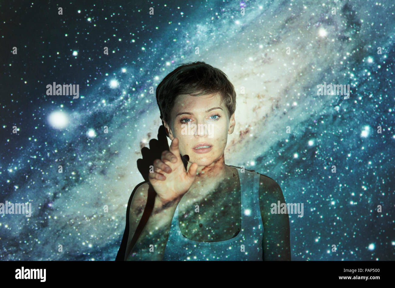 Portrait of blond woman, projection of milky way, imaginary touchscreen - Stock Image