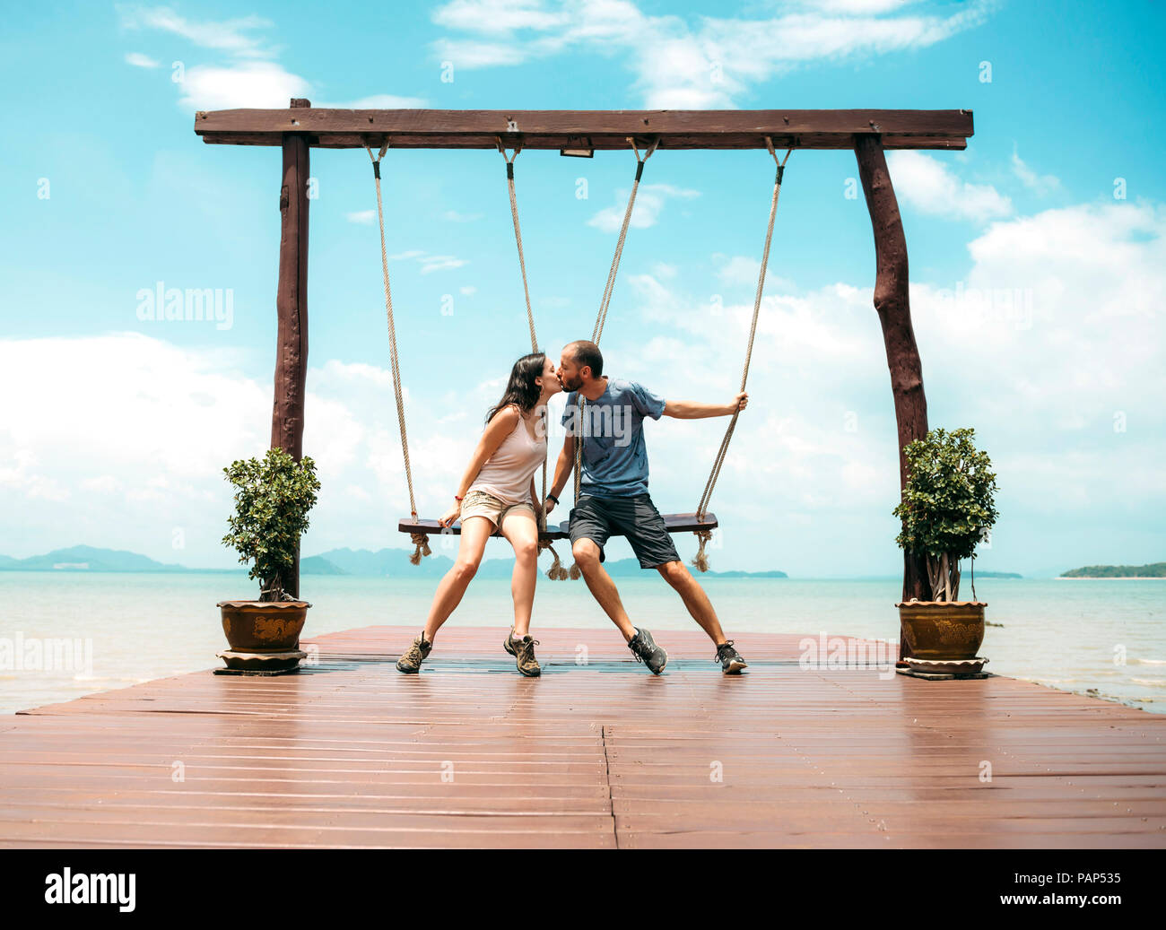 Thailand, Koh Lanta, kissing couple sitting on swings in front of the sea - Stock Image