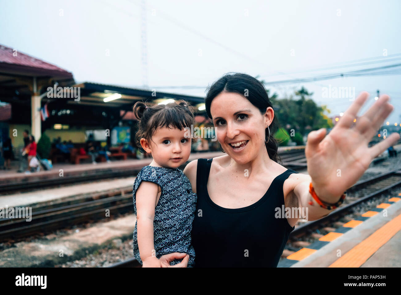 Thailand, Ayutthaya, portrait of mother and little daughter saying goodbye at a train station - Stock Image