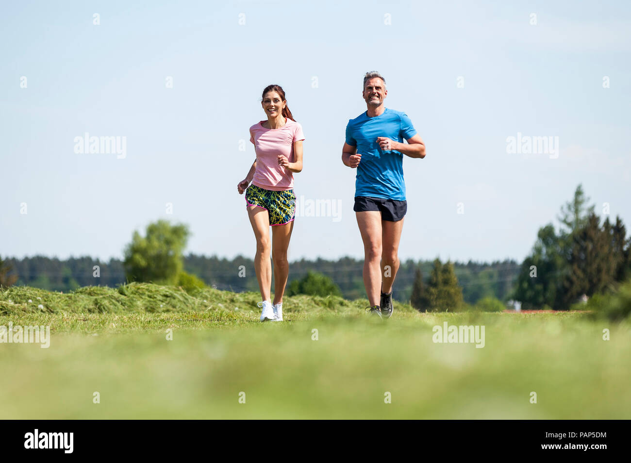 Couple running on field path - Stock Image