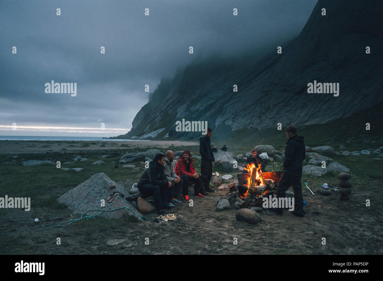 Norway, Lofoten, Moskenesoy, Group of young men sitting at a campfire at Bunes Beach - Stock Image