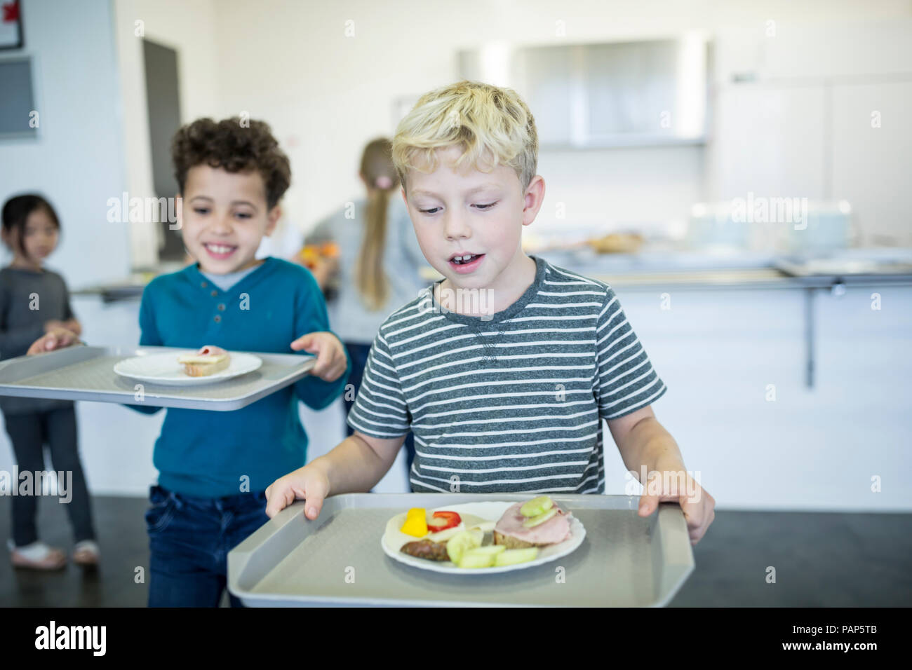 Pupils carrying trays in school canteen - Stock Image