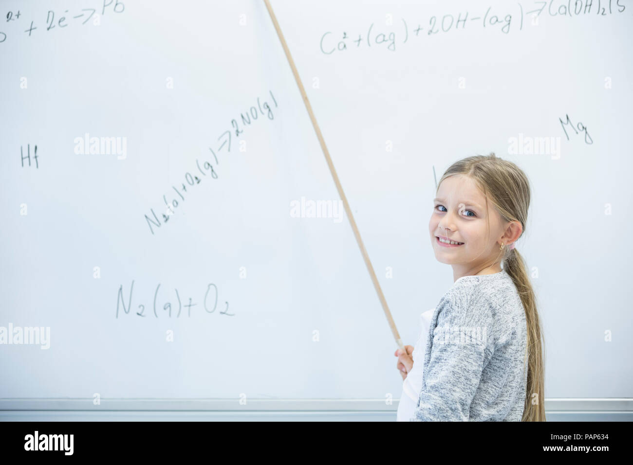 Smiling schoolgirl explaining formula at whiteboard in class - Stock Image