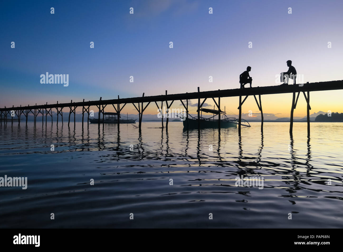 Silhouette of two teen boys sitting and visiting on an island dock, with purple sunrise - Siargao, Philippines - Stock Image