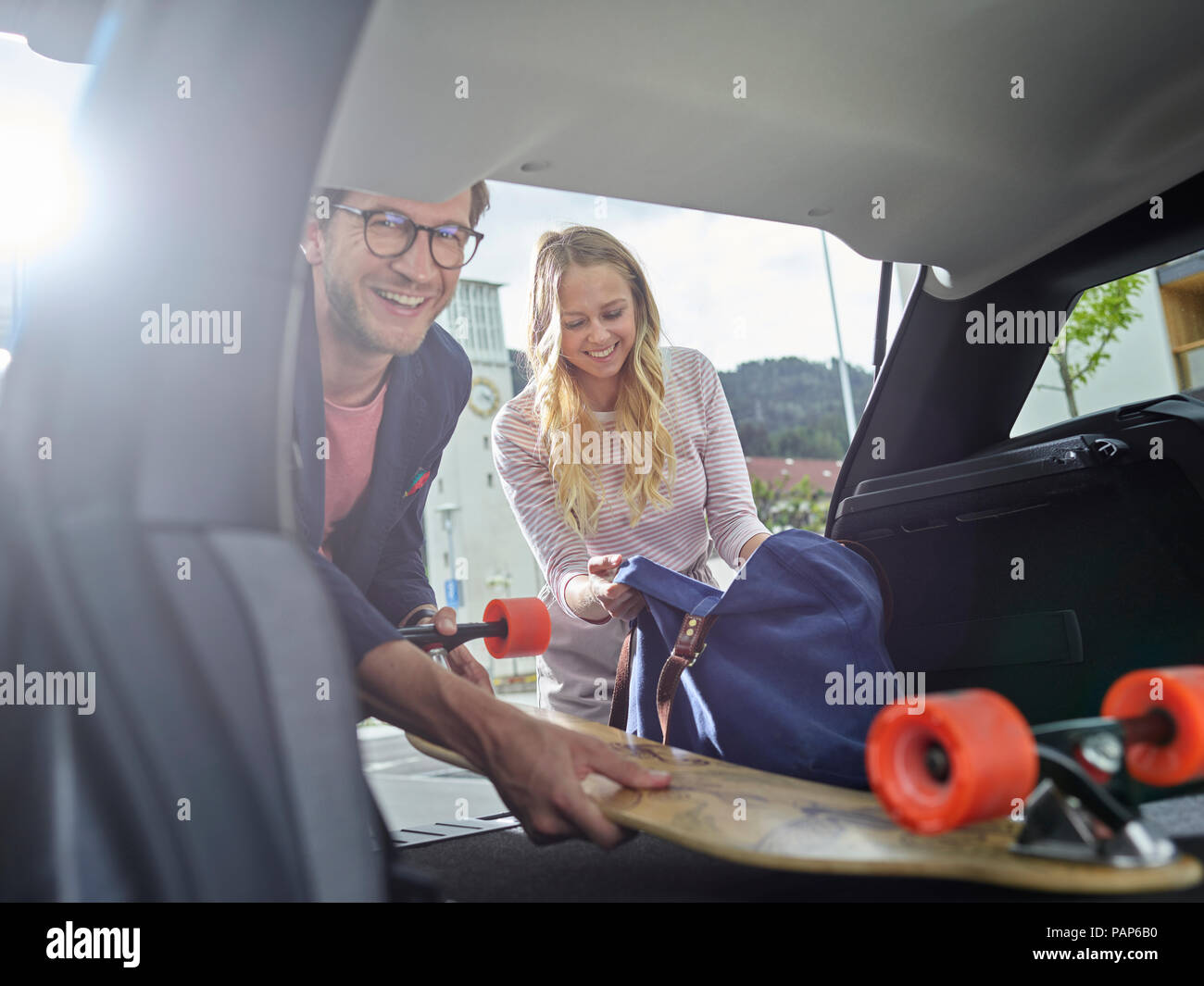 Smiling couple loading boot of electric car - Stock Image