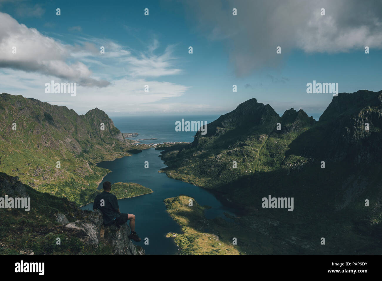 Norway , Lofoten, Traveller sitting on rock, looking over Agvatnet lake - Stock Image