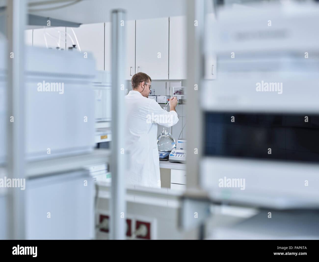 Chemist working in laboratory - Stock Image