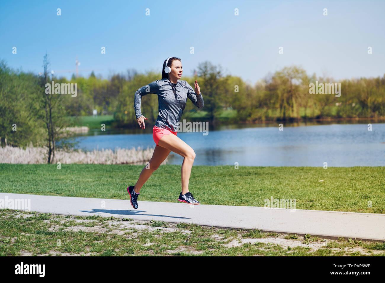 Female jogger running at park - Stock Image