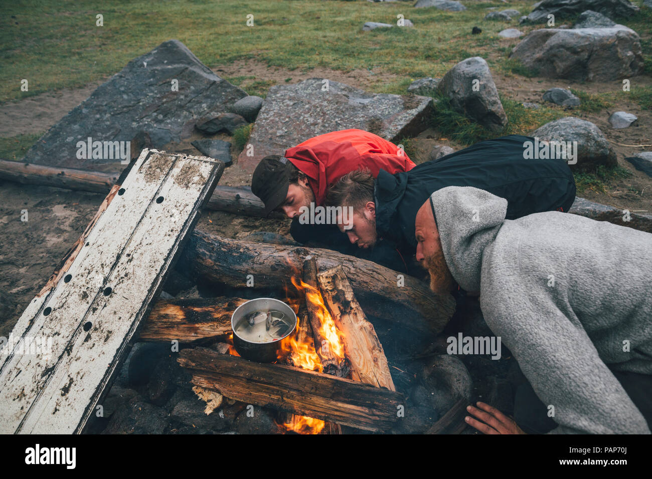 Norway, Lofoten, Moskenesoy, Three men fanning the flames of a camp fire at Bunes Beach - Stock Image