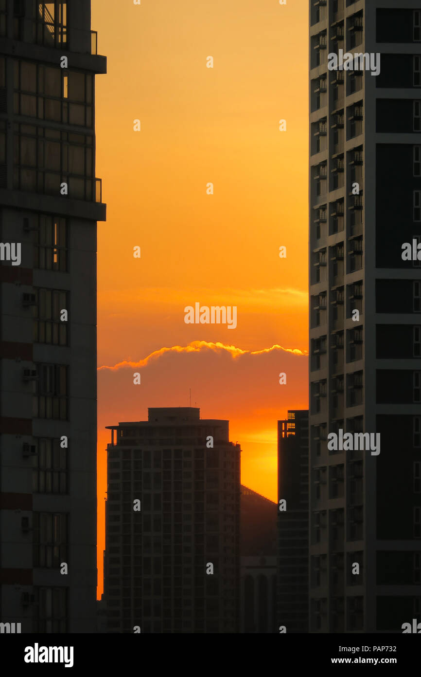 Fiery orange sunset between the windows of tall buildings in Pasig, Manila - Philippines - Stock Image