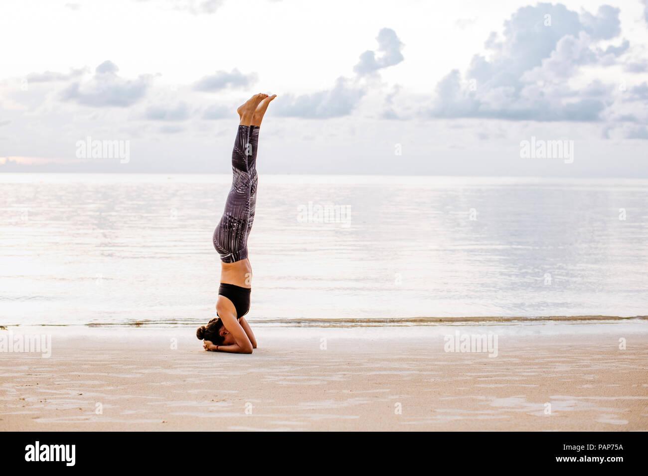 Thailand, Koh Phangan, Sportive woman doing yoga on the beach - Stock Image