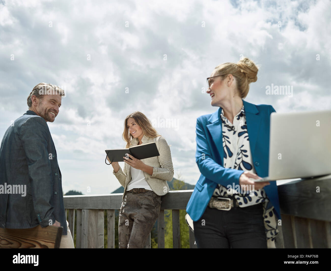 Smiling colleagues with laptop standing outside talking - Stock Image