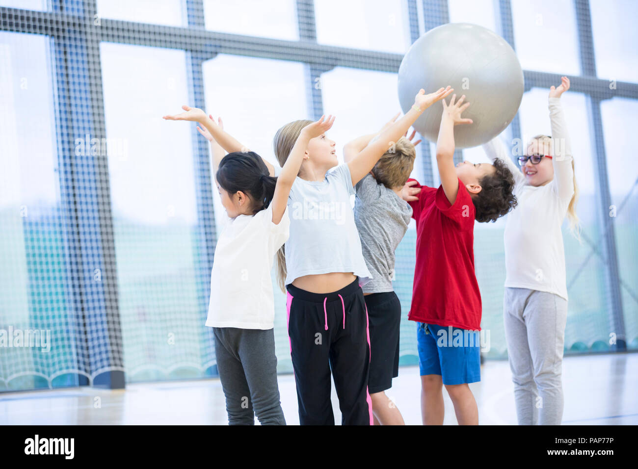 Pupils handing over gym ball in gym class - Stock Image