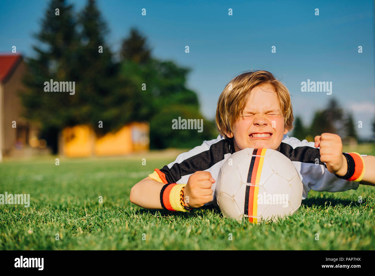 Boy in German soccer shirt lying on grass, keeping fingers crossed for world championship - Stock Image