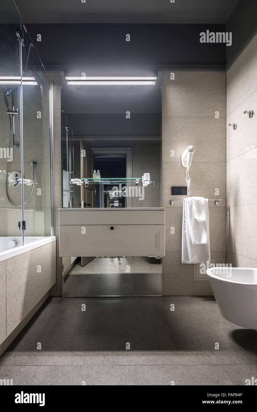 Bathroom in a hotel with light tiled walls. There is a bath with a ...