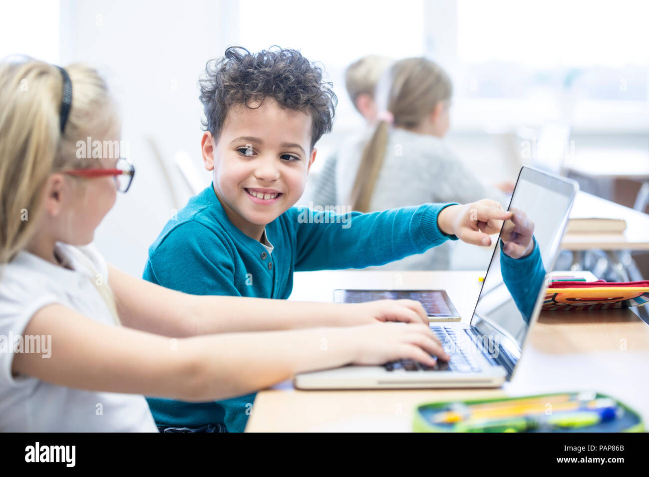 Schoolboy and schoolgirl using laptop together in class - Stock Image
