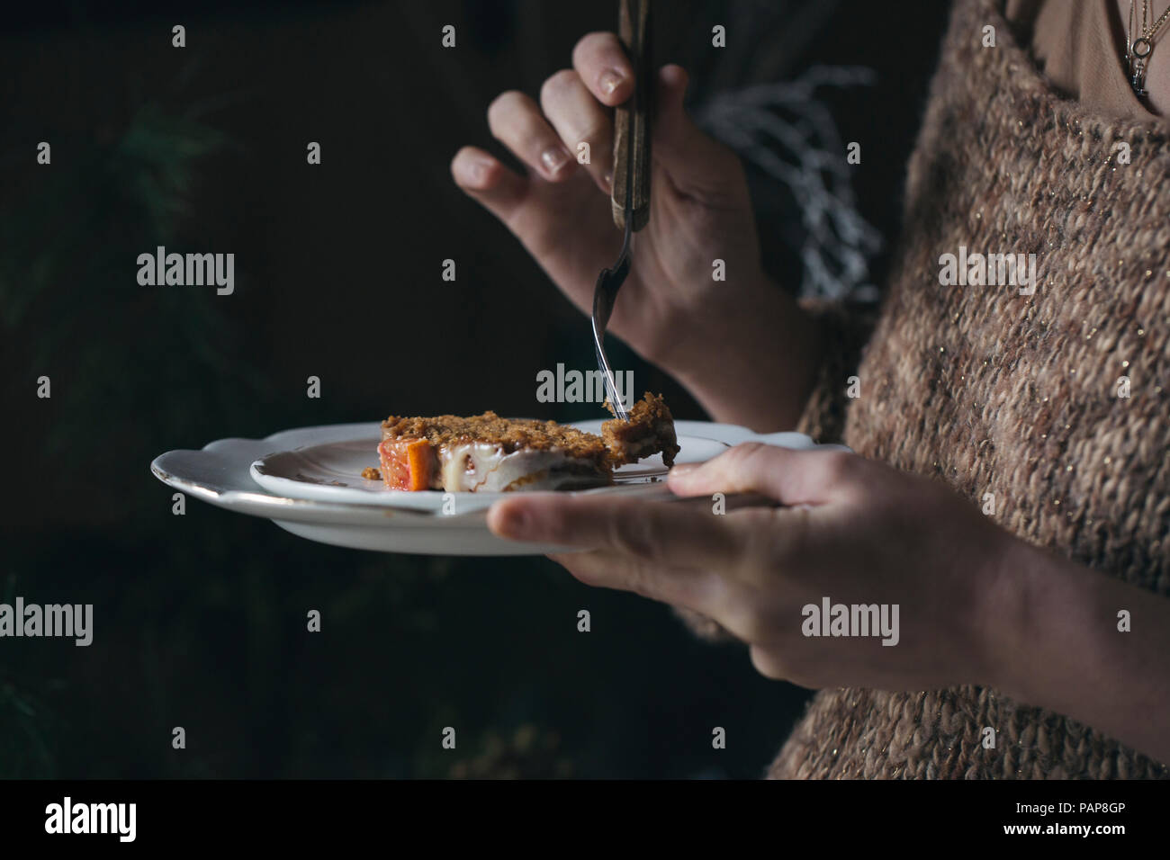 Woman eating home-baked Christmas cake, partial view - Stock Image